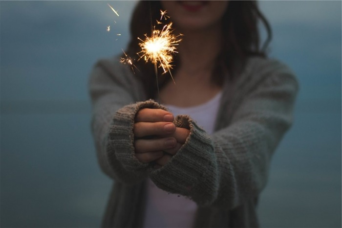 young-woman-holding-sparkler-at-night